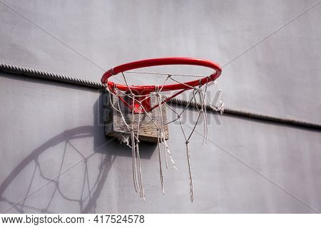Red Basketball Hoop Attached To Gray Metal Wall