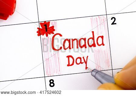 Woman Fingers With Pen Writing Reminder Canada Day In Calendar. July 01