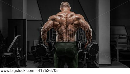 Powerful Bodybuilder Posing In The Gym With Dumbbells. No Name Portrait. Back View. Bodybuilding Con