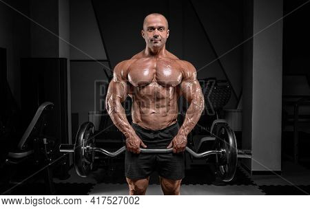 Professional Weightlifter Posing In The Gym With A Barbell In His Hands. Classic Bodybuilding.