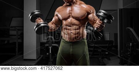 Powerful Bodybuilder Works Out In A Gym With Dumbbells. No Name Portrait. Bodybuilding Concept. Mixe