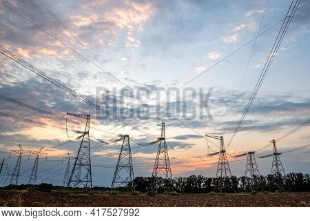 Electrical Pylons And High Voltage Power Lines At Sunset Background. Group Silhouette Of Transmissio