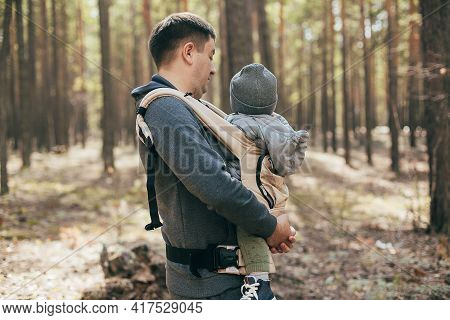 Father Carrying His Baby Boy In Ergo Bag. Lifestyle, Authentic Moment. Concept Of Togetherness, Care
