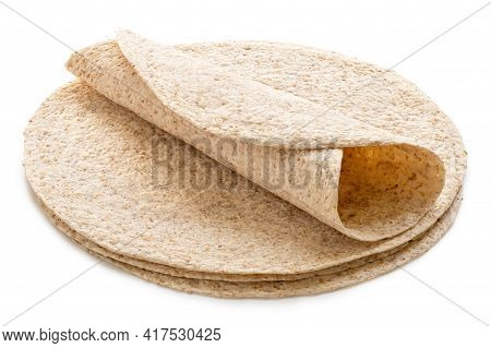 Rolled Up Tortilla On Top Of A Stack Of Plain Spelt And Oat Tortilla Wraps Isolated On White.
