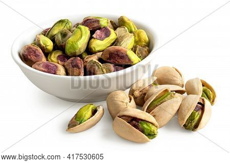 Shelled Pistachios In A White Ceramic Bowl Next To Pistachios In Shell Isolated On White.