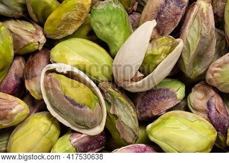 Background Of Shelled Pistachios And Two Open Pistachios. Top View.