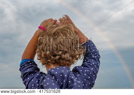 Curly Hairs Of Little Kid Rising Hands Up And Looking Into Cloudy Sky With Sun Rays And Rainbow. Chi