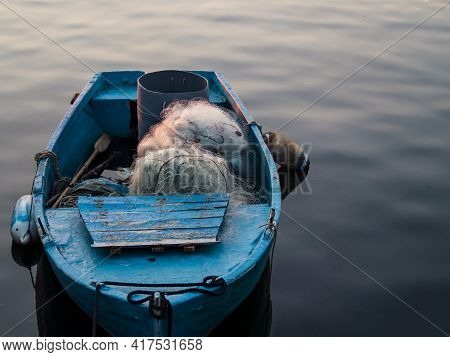 Typical Fishermen Boat With Nets And Wooden Oars Moored On A Pier