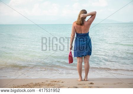 A Woman Holds In Her Hand A Mesh Shopping Bag And Stands On The Edge Of The Sea On A Sandy Beach. Ec