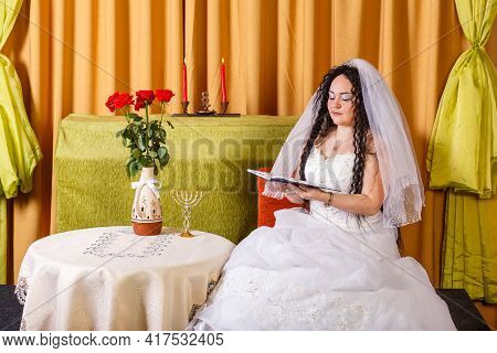 A Jewish Bride In A White Wedding Dress With A Veil Sits At A Table With Flowers And Reads Blessings