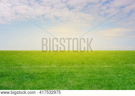 Green Grass And Blue Sky With Sunbeams. Empty Field With Grass In Summer. Colorful Green Meadow. Nat