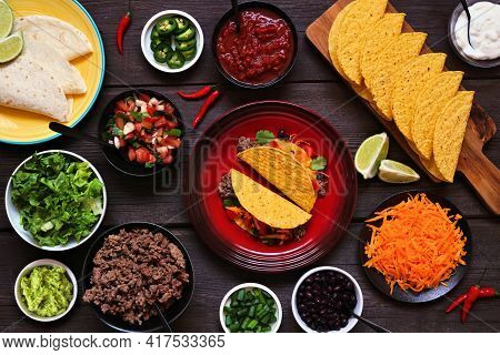 Taco Bar Table Scene With A Selection Of Ingredients. Above View On A Dark Wood Banner Background. M