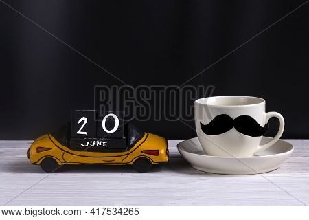Wooden Car With Father's Day Celebration Date June 20 And A Cup Of Coffee With A Pasted Black Mustac