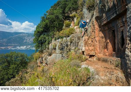Hiking Lycian way. Man is descending tricky path on cliff high above Mediterranean sea near ancient rock tomb of Saba in Ancient Sites on Lycian way trail, Trekking in Turkey, outdoor activity