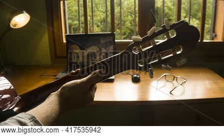 Man Studying Guitar On-line With Laptop And Professor
