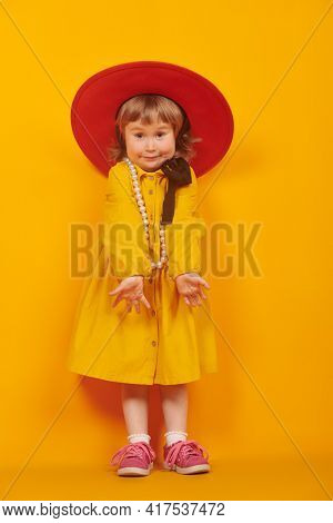 Cute little girl fashionista. Full length portrait of a lovely little girl in red hat and yellow dress looking at the camera and is surprising. Happy childhood.