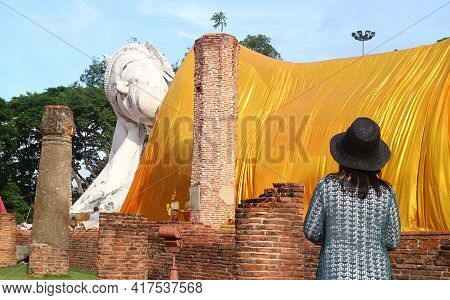 Female Visitor Looking Up To The Largest Reclining Buddha Image In Thailand At Wat Khun Inthapramun