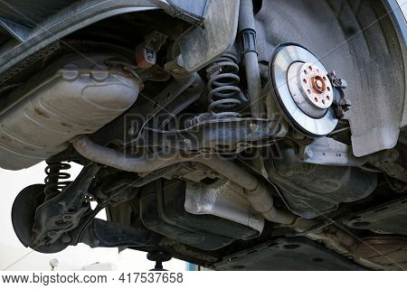 A Car In A Car Service Is Lifted On A Lift For Repair. Bottom View Of The Car. Vehicle Underbody, Re