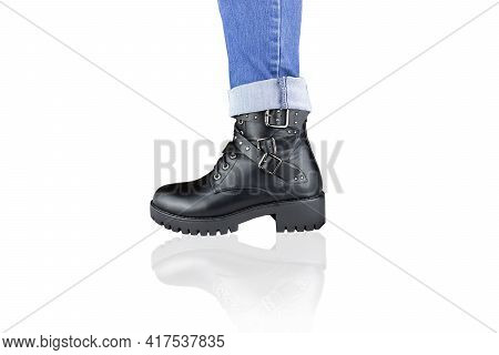 Leg In Blue Jeans And Black Lace-up Boot With Buckles And Straps. Isolated On White.