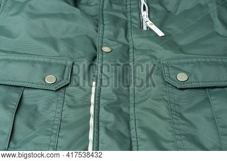 Fragment Of A Green Jacket Made Of Waterproof Fabric With High-quality Seams, Pockets, Metal Buttons