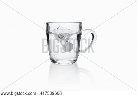 Soluble Tablet Sinking With Splash To Transparent Glass Mug On White Background.