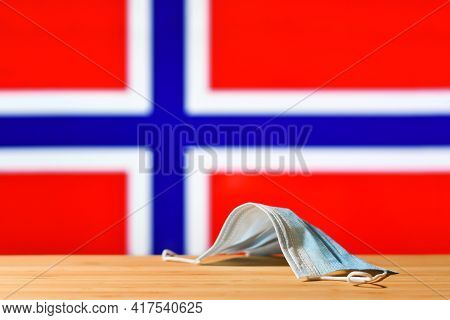A Medical Mask Lies On The Table Against The Background Of The Flag Of Norway. The Concept Of A Mand