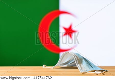 A Medical Mask Lies On The Table Against The Background Of The Flag Of Algeria. The Concept Of A Man