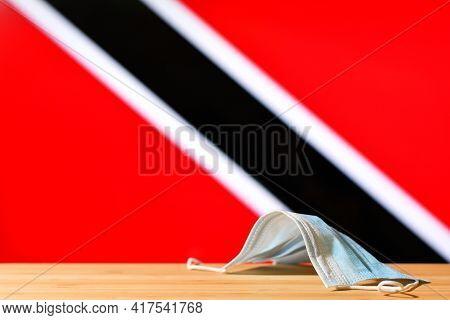 A Medical Mask Lies On The Table Against The Background Of The Flag Of Trinidad And Tobago. The Conc