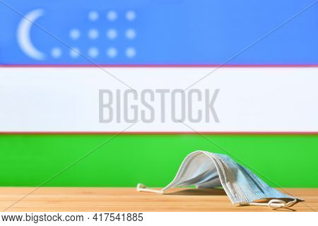 A Medical Mask Lies On The Table Against The Background Of The Flag Of Uzbekistan. The Concept Of A