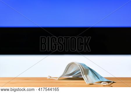 A Medical Mask Lies On The Table Against The Background Of The Flag Of Estonia. The Concept Of A Man
