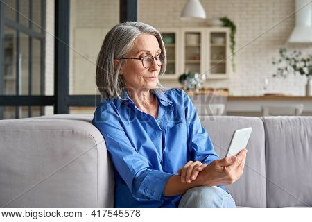 Serious Mature Middle Age Senior Woman At Home On Couch Holding Mobile Cellphone, Reading News Or Wa