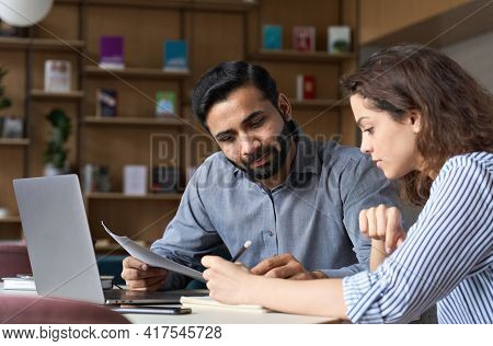 Two Multiethnic Professionals Colleagues Working Together With Laptop And Papers In Office. Indian M