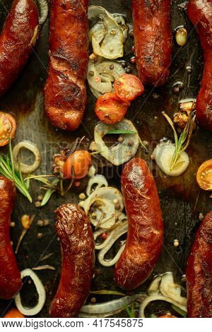 Tasty grilled homemade rosemary sausages placed on iron frying tray over rustic dark stone table