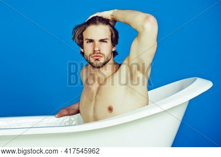 Young Man With Muscular Body Sitting In Bath Tub. Sexy Man Beauty, Relax And Hygiene, Healthcare, Co