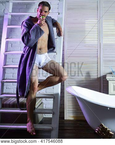 Sexy Man With Apple In Bathroom. Man With Fit Body Eat Apple In Underwear, Bathrobe, Food. Health, B