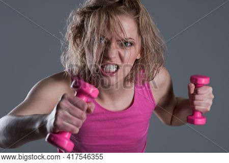 Woman Coach With Angry Face Holds Dumbbells On Grey Background. Excited Girls Power Concept. Girl Do