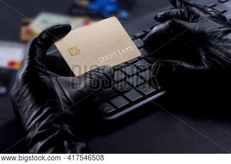 Internet Theft - Thief's Gloved Hands With Credit Card Behind Laptop