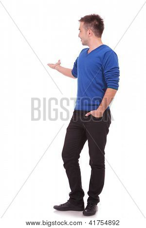 Full length of smiling young man in casual clothes presenting your product over white background