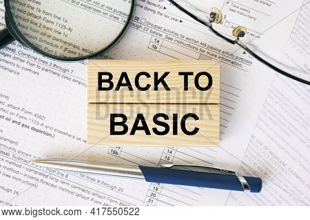 Wooden Blocks With Text Back To Basic On Financial Docs. Notepad, Magnifying Glass Eyeglasses And Bl
