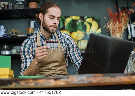 Bearded Salesman Using Wireless Laptop At Decor Store For Registration Discount Card Of Regular Cust