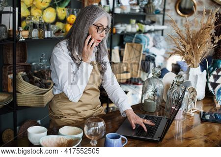 Professional Saleswoman With Grey Hair Sitting At Decor Shop With Opened Laptop And Talking On Mobil