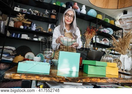 Aged Woman In Eyeglasses And Apron Holding In Hands Beautiful Vase And Smiling On Camera. Pretty Sal
