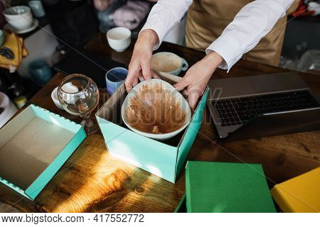 Close Up Of Hands Of Sales Manager Woman In Apron Packing Beautiful Ceramic Plate In Paper Box At De