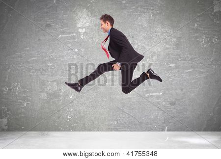 young business man in a big run over a gray background