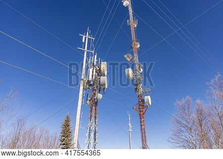 A Clear Shot Featuring Two Tall Communication Towers, Providing Wireless Cellular Services, With Tre