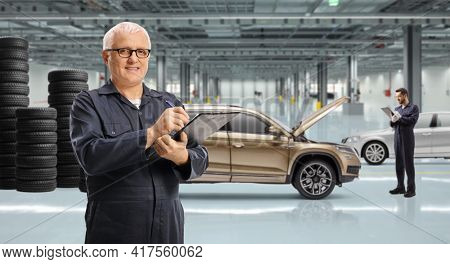 Auto repair garage with a suv and piles of tires and auto mechanic workers