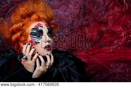 Red-haired young woman in witch costume. Creative makeup for masquerade.