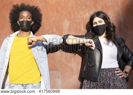 Couple Of Multiethnic Friends Wearing Protective Masks Greet Each Other By Bumping Elbows And Keepin