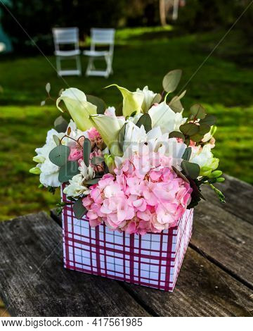 Flowers in gift box outside on wooden table with text space