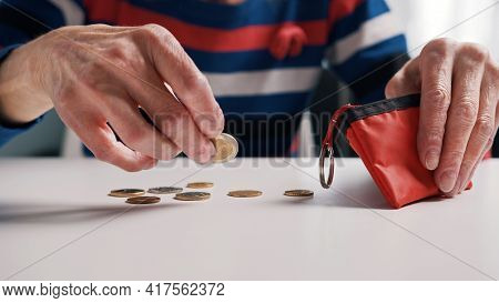 Poor Old Woman Counting Coins On The Table. Low Pension And Insufficient Funds. High Quality Photo